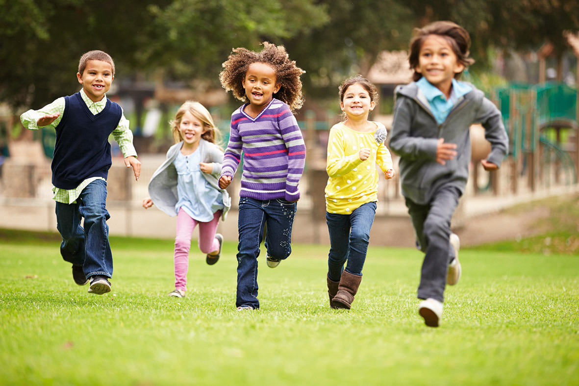 Children running towards camera in park